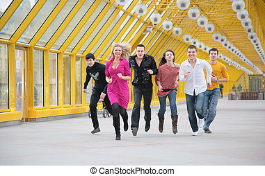 group of friends runs on yellow footbridge