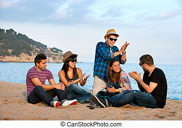 Group of friends singing on beach.