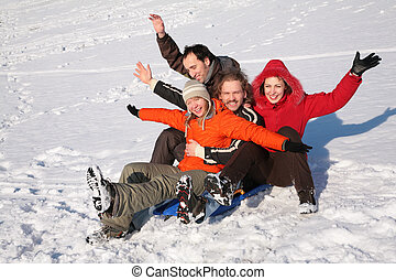 group of friends sit on plastic sled on snow