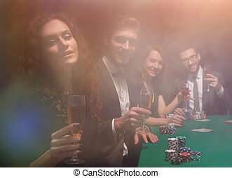 group of friends sitting at game table in casino