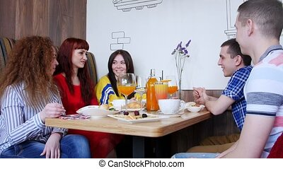 Group of friends sitting in a cafe and having a conversation