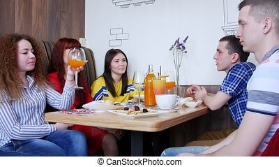 Group of friends sitting in a cafe and talking. A young woman takes a glass with drink in it