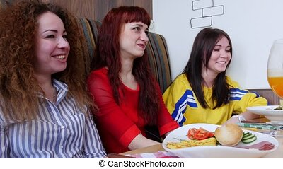 Group of friends sitting in a cafe. Three women talking to their friends and laughing