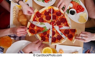 Group of friends sitting in cafe. Taking pieces of pizza...