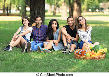 Group of friends sitting in park on grass and looking at ...