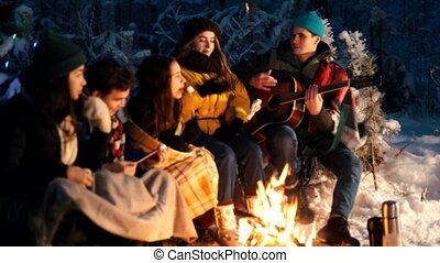 Group of friends sitting in winter forest by the fire. A young man holding guitar