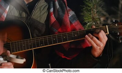 Group of friends sitting in winter forest by the fire. A young man playing guitar