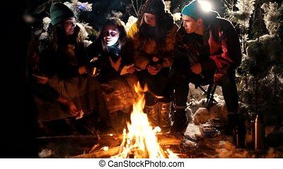Group of friends sitting in winter forest by the fire. A young woman telling her friends a scary story