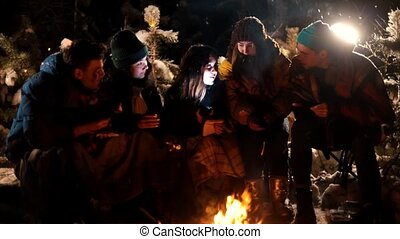 Group of friends sitting in winter forest by the fire. A young woman telling her friends a scary story, holding a flashlight near her face