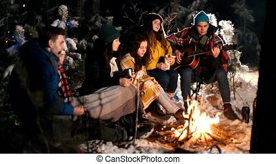 Group of friends sitting in winter forest by the fire and eating marshmallows on skewers. A young man playing guitar