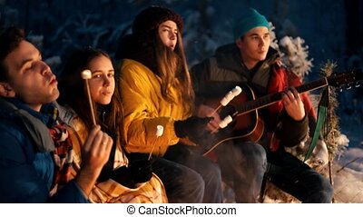 Group of friends sitting in winter forest by the fire and eating marshmallows on skewers. A young man holding guitar