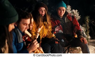 Group of friends sitting in winter forest by the fire. Frying different types of food