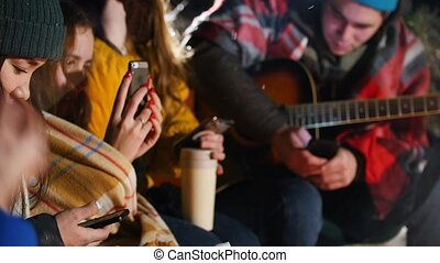 Group of friends sitting in winter forest by the fire. Sitting in their phones. Close up