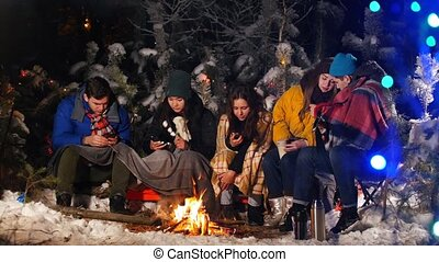 Group of friends sitting in winter forest by the fire. Sitting in their phones.