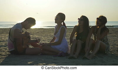 Group of friends sitting on the beach and singing with a guitar