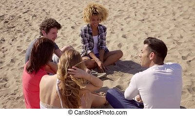 Group of friends sitting talking on the beach