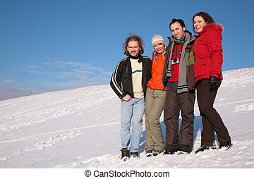 group of friends stand on snow on hillside