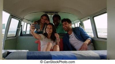 Group of friends taking selfie in camper van 4k