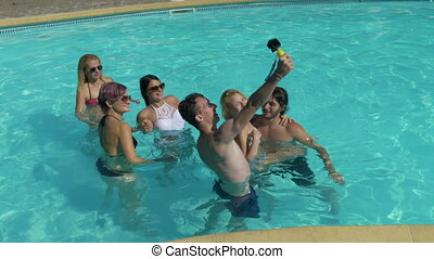 Group of friends taking selfie in the pool water at the villa