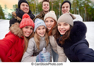 group of friends taking selfie outdoors in winter