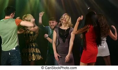 Group of friends talking while dancing to the music. Action takes place in a nightclub. Slow motion