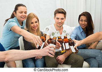 Group Of Friends Toasting Beer Bottles