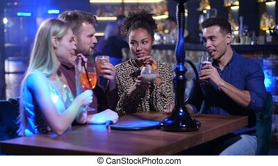 Group of friends toasting, clinking glasses in bar - Diverse...