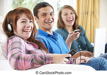 Group Of Friends Using Digital Technology At Home