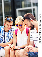 Group of friends using smartphone in the campus