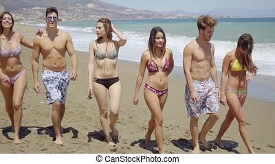 Group of Friends Walking Together on Sunny Beach