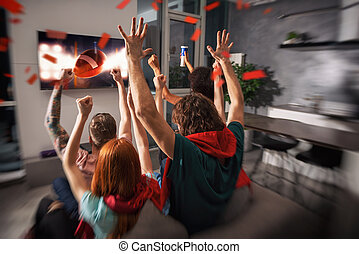 Group of friends watch a football game together on television and rejoice