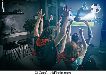 Group of friends watch the game together on television and rejoice