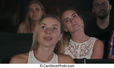 Group of friends watching a movie at the cinema theater and applauding at the end