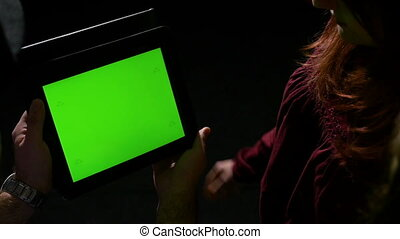 Group of friends watching online content on a green screen tablet pc and talking about it