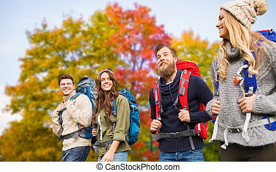 group of friends with backpacks hiking in autumn