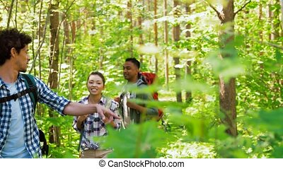 group of friends with backpacks hiking in forest - travel,...