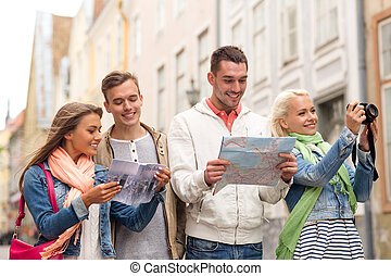 group of friends with city guide, map and camera