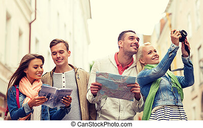 group of friends with city guide, map and camera - travel,...