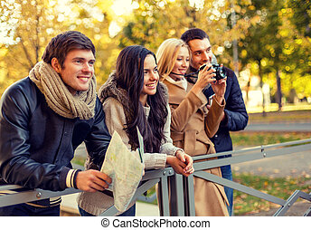 group of friends with map and camera outdoors