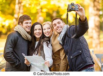 group of friends with photo camera in autumn park