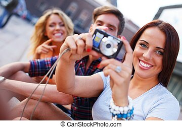 Group of friends with photo camera outdoors