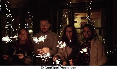 Group of friends with sparkles having party on New Years Eve.