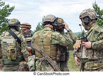 Group of fully armed american soldiers getting ready for the fight on military range, active military game airsoft.