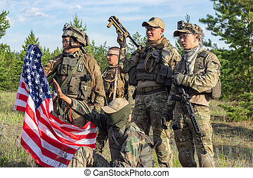 Group of fully armed american soldiers with US flag after winning the team game airsoft on military range