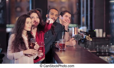Group of girls and boys at the bar cheering for their football team