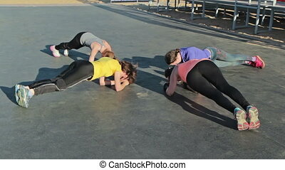 Group of girls are practicing the plank pose, - Group of...