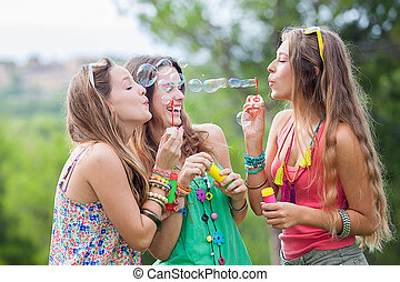 group of girls blowing bubbles at music festival