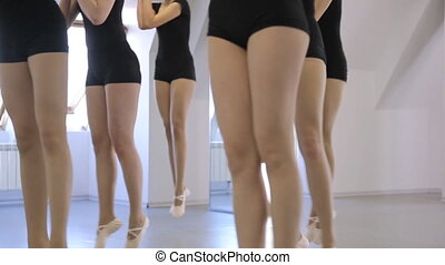 Group of girls in same black costumes performs exercise in dancing class