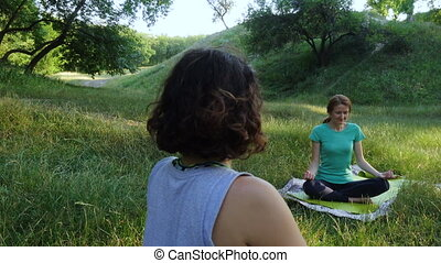 group of  girls practicing yoga exercises outdoors