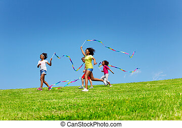 Group of girls run fast waving with color ribbons